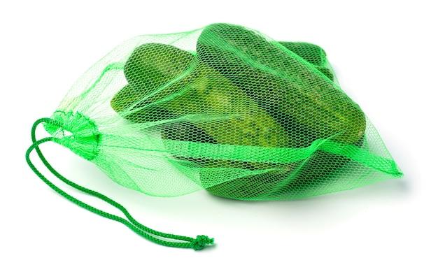 Bio-netz zum einkaufen von gemüse. gurken im gitter. isoliert auf weißem hintergrund.