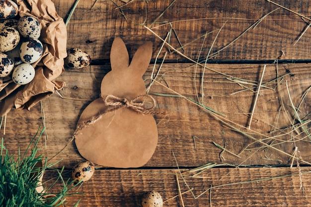 Bio ostern. draufsicht auf wachteleier in zerknittertem braunem papier und esterhase, die auf rustikalem holztisch liegen lying