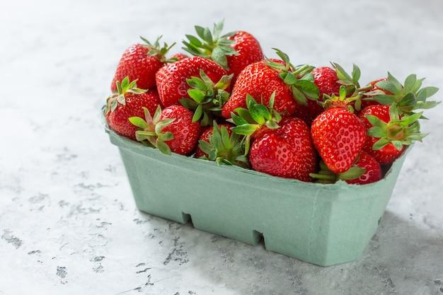Bio reife erdbeeren in einem biologisch abbaubaren behälter