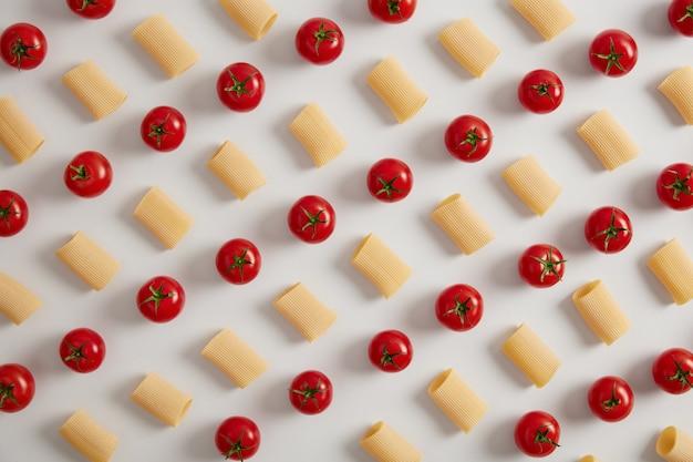 Bio-rigatoni-nudeln und rote kirschtomaten in reihen auf weißem hintergrund angeordnet. kreatives layout für das menü. lebensmittelkonzept. gesunde trockene makkaroni-nudeln. oben aufnahme, blick von oben