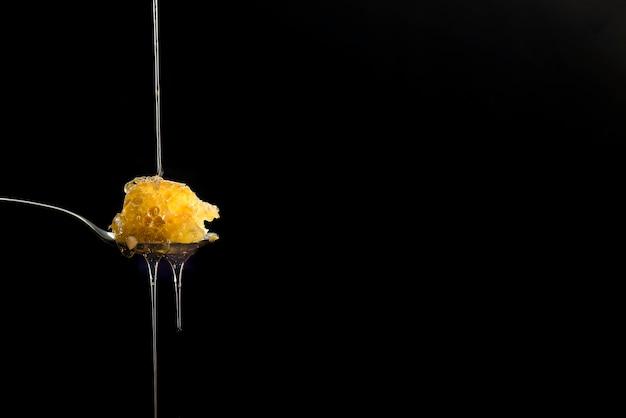 Bio rohe bienenwaben auf löffel mit honigtropfen, reine, süße güte