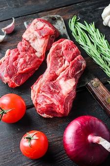 Bio rohes chuck eye roll rindersteak über altem metzgerbeil mit rosmarinrotem onin, knoblauchpfefferkörnern und tomaten auf altem dunklem holztisch. seitenansicht.