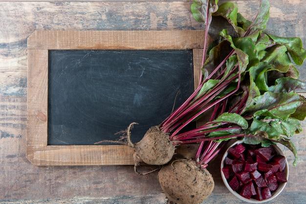 Bio-rote-bete-wurzeln mit salat und schultafel