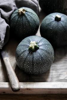 Bio runde zucchini in holzkiste