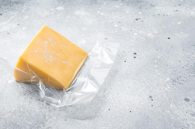 Bio-scharfer cheddar-käse in vakuumverpackung. grauer hintergrund. ansicht von oben. platz kopieren.