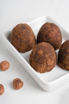 Bio-schokoladen-trüffel-dessert aus haselnuss mit kakaopulver auf einem teller serviert