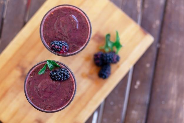 Bio-smoothie mit brombeeren, kirschen, blaubeeren und spinat. gesundes essen. smoothie-schüssel. draufsicht auf holzhintergrund