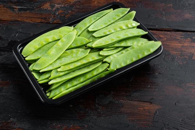 Bio-snap sugar peas ready-to-eat-set in einem plastikbehälter auf einem alten dunklen holztisch