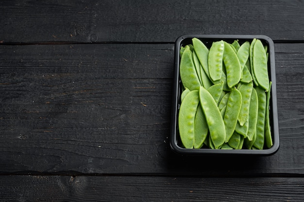 Bio-snap sugar peas ready-to-eat-set in plastikbehälter auf schwarzem holz