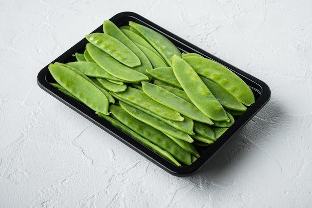 Bio-snap sugar peas ready-to-eat-set in plastikbehälter auf weißem stein