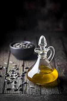 Bio-sonnenblumenöl in einem kleinen glas mit sonnenblumenkernen auf dunklem holzhintergrund