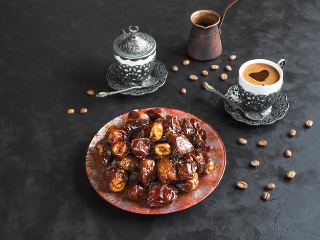 Bio süße datteln mit sirup und schwarzem kaffee. ramadan kareem urlaubskonzept.