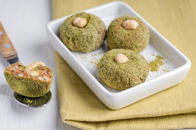Bio süße vegane nusstrüffel aus cashew in grünem pulver serviert auf teller mit löffel auf dem tisch