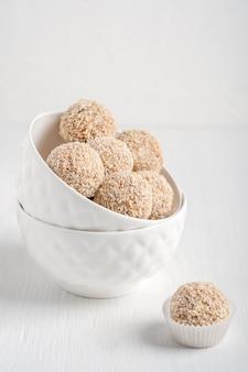 Bio süße vegane nusstrüffel aus haselnuss und früchten serviert in zwei schalen auf einem weißen tisch