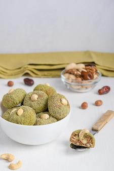 Bio süße vegane trüffel aus cashew und walnuss in grünem pulver serviert in schüssel mit löffel