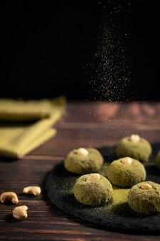 Bio-süße vegane trüffel mit cashew und grünen pulverstreuseln auf dunklem holztisch serviert