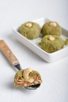 Bio süße vegetarische trüffel aus cashew in grünem pulver serviert auf teller mit löffel