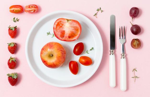 Bio-tomaten und apfel auf einem teller