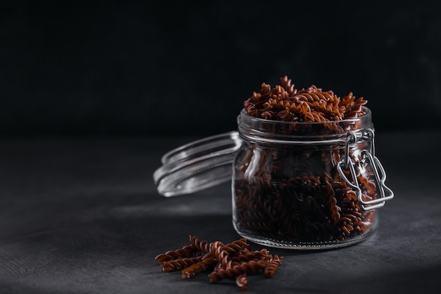Bio ungekochte buchweizen-fusilli-nudeln in einem glas auf dunklem hintergrund. vollkorn glutenfreie nudeln. gesundes lebensmittelkonzept.