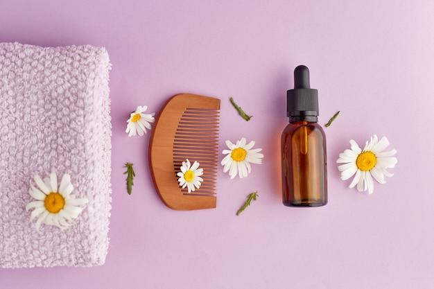 Bio-vegane naturkosmetik für haare flache zusammensetzung von kamillenblüten und kosmetikflaschen mit ätherischem öl draufsicht der natürlichen schönheit platz für text