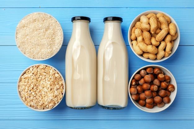 Bio vegane nichtmilch mit glasmilchflasche und massenprodukten auf hölzernem hintergrund
