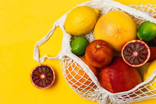 Bio-zitrusfrüchte in wiederverwendbarer einkaufstasche aus baumwollgewebe