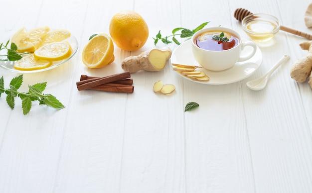 Bio-zutaten für gesunden heißen tee auf weißem holztisch. immunverstärkendes mittel