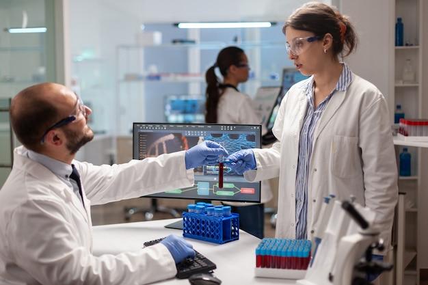Biochemie-forscher, die experimente mit blutproben für die impfstoffentwicklung durchführen. mediziner, der in einem modern ausgestatteten labor mit high-tech-technologie mit dna-scan-bildern arbeitet.