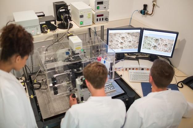 Biochemiestudenten, die großes mikroskop und computer an der universität verwenden