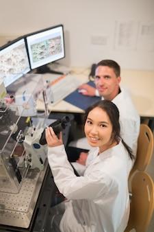Biochemiestudenten, die großes mikroskop und computer verwenden