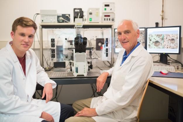 Biochemiker, der großes mikroskop und computer mit studenten verwendet