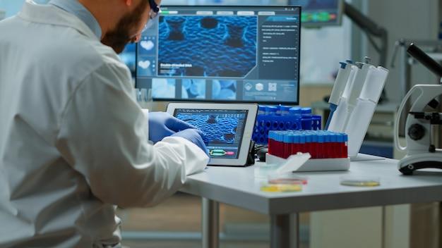 Biochemiker, der manifestationen von viren überprüft, die in tablette mit spezieller software im chemielabor suchen. gruppe von ärzten, die die entwicklung von impfstoffen mit hilfe von high-tech-forschungsdiagnosen untersuchen