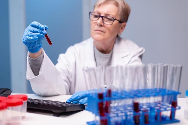 Biochemiker im weißen kittel entdeckt genetische infektionen und analysiert ein blutröhrchen