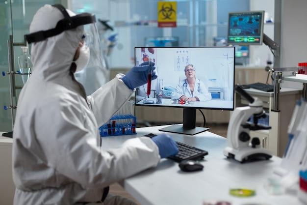 Biologe, der ein medizinisches reagenzglas mit infiziertem blut hält und mit dem forscher diskutiert