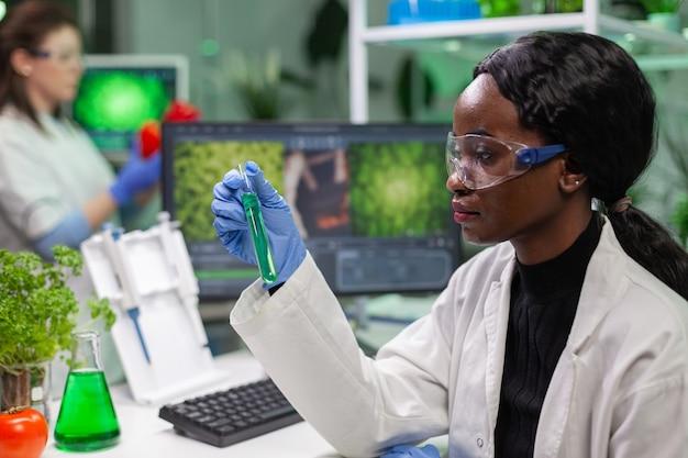Biologe, der ein reagenzglas mit genetischer flüssigkeit hält, das grüne dna-probe auf biochemisches fachwissen untersucht