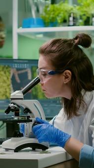 Biologe, der eine blattprobe in ein mikroskop nimmt und chemische flüssigkeit beobachtet