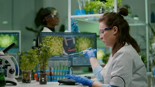 Biologe, der lösungsflüssigkeit in ein reagenzglas gibt