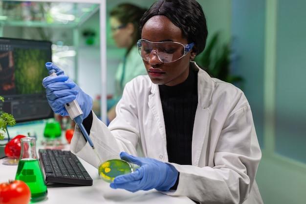 Biologe wissenschaftler afrikanische forscherin, die genetische lösung aus dem reagenzglas nimmt