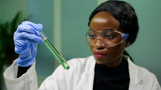Biologenfrau, die reagenzglas mit genetischer flüssigkeit hält, die grüne dna-probe untersucht