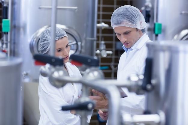 Biologerteam, das haarnetz in der fabrik spricht und trägt