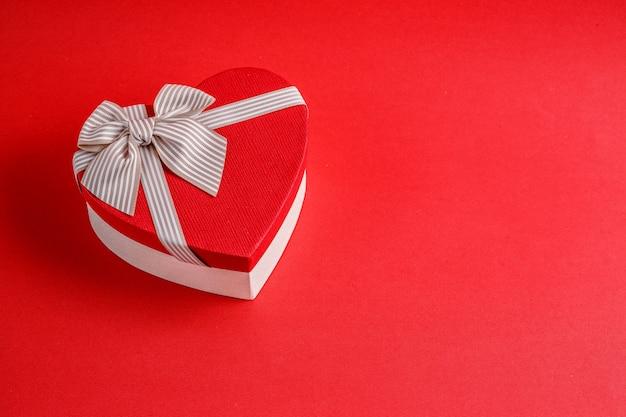 Biologisch abbaubare pappgeschenkbox in form eines herzens mit bändern auf rot
