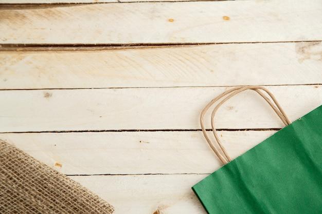 Biologisch abbaubare umweltfreundliche papptasche auf hölzernem hintergrund