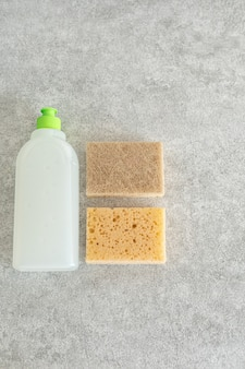 Biologisch abbaubares geschirrspülgel und schaumschwamm auf einem steintisch. das konzept der reinigung und aufrechterhaltung der sauberkeit.