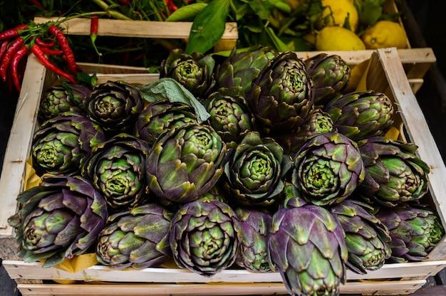 Biologische, natürlich angebaute artischocke auf einem marktschalter. gemüse vom bauernmarkt. ökologische produkte.