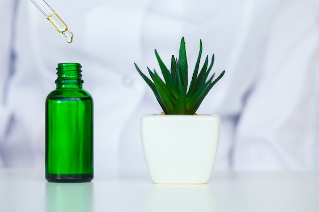 Biologischer test. frau, die flasche im labor hält. der wissenschaftler, dermatologe, testet das bio-naturprodukt im labor