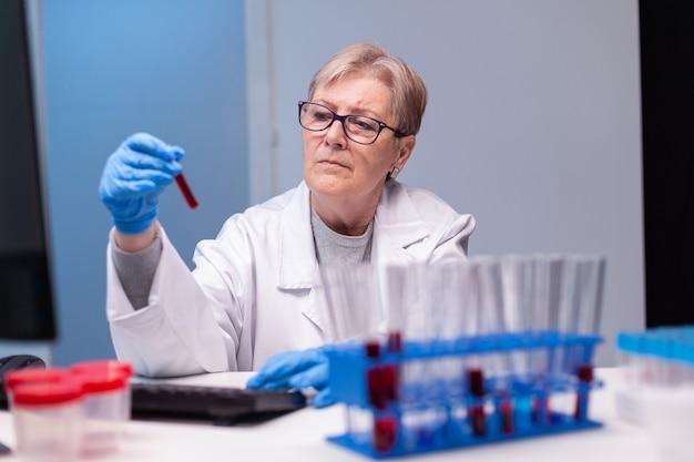 Biotechnologe leitender arzt, der ein blutröhrchen für die medizinische untersuchung analysiert