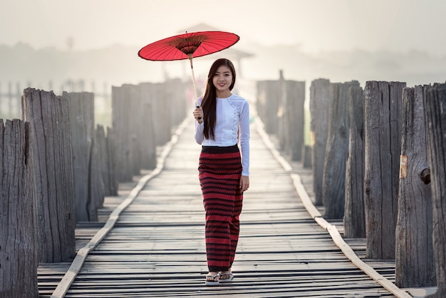 Birmanische frau, die traditionellen roten regenschirm hält und auf brücke u bein geht
