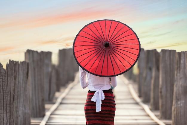 Birmanische frau, die traditionellen roten regenschirm hält und auf brücke u bein, mandalay, myanmar geht