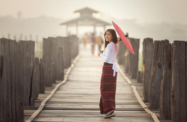 Birmanische frau, die traditionellen roten regenschirm hält und auf brücke u bein, myanmar geht