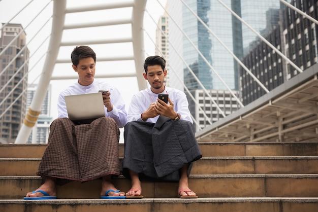 Birmanische geschäftsleute benutzen smartphone in der stadt